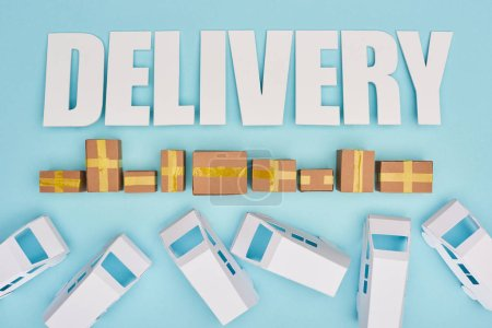 Photo for Delivery inscription near closed cardboard boxes and mini vans on blue background - Royalty Free Image