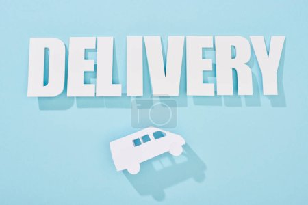 Photo for White delivery inscription with shadow above mini van on blue background - Royalty Free Image