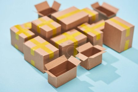 Photo for Miniature cardboard postal boxes on blue background - Royalty Free Image