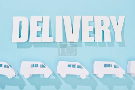 Photo for White delivery inscription with shadow above mini vans on blue background - Royalty Free Image