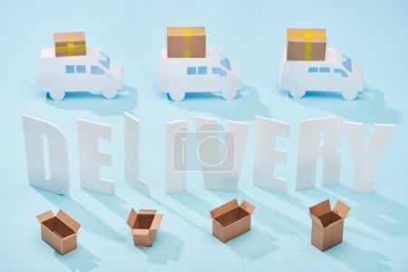 Photo pour Inscription blanche de livraison entre les mini-camions et les boîtes en carton ouvertes sur le fond bleu - image libre de droit