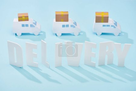 Photo for White delivery inscription under mini trucks with cardboard boxes on blue background - Royalty Free Image