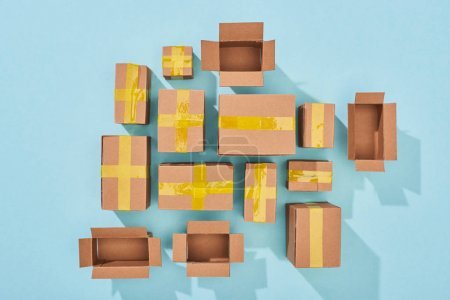 Photo for Top view of closed and open cardboard boxes on blue background - Royalty Free Image