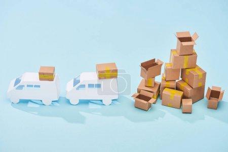 white mini vans near pile of cardboard boxes on blue background