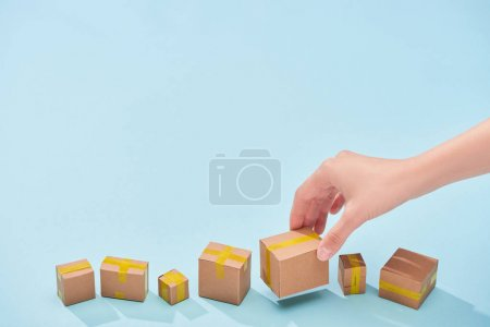 Photo for Cropped view on woman holding closed cardboard box on blue background - Royalty Free Image