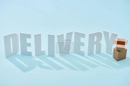 Photo pour Boîtes en carton l'un sur l'autre près de blanc inscription de livraison sur fond bleu - image libre de droit