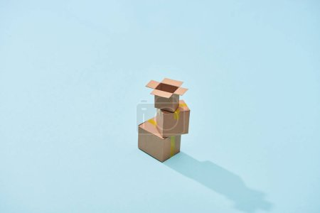 Photo for Miniature carton boxes on blue background with copy space - Royalty Free Image