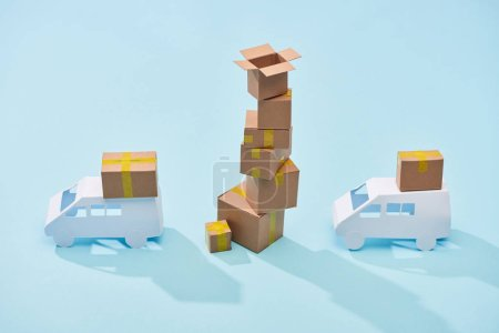 pile of cardboard boxes between white trucks on blue background