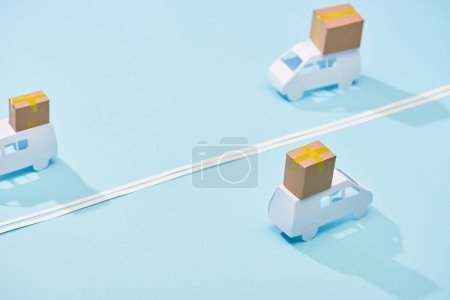 Photo for Miniature white trucks with parcels on blue background with double line - Royalty Free Image