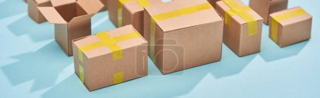 Photo for Panoramic shot of cardboard postal boxes on blue background - Royalty Free Image