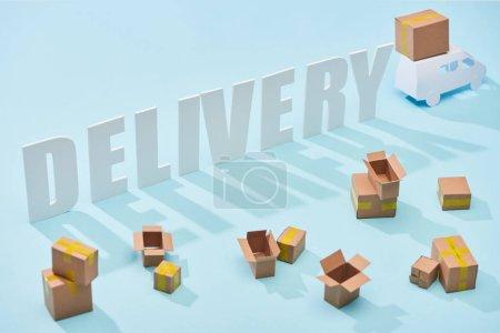 Photo pour Inscription blanche de livraison près du mini camion avec des boîtes en carton sur le fond bleu - image libre de droit
