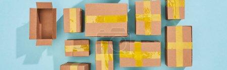 Photo pour Plan panoramique de boîtes miniatures en carton sur fond bleu - image libre de droit