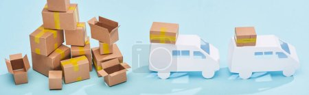 Photo for Panoramic shot of pile of cardboard boxes near mini trucks on blue background - Royalty Free Image