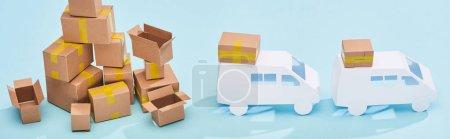 panoramic shot of pile of cardboard boxes near mini trucks on blue background