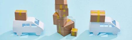 Photo pour Coup panoramique de boîtes en carton un sur l'autre près de mini-camions sur fond bleu - image libre de droit