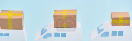 panoramic shot of miniature trucks with cardboard parcels on blue background