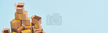 Photo for Panoramic view of pile of cardboard boxes on blue background with copy space - Royalty Free Image