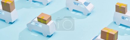 Photo for Panoramic shot of miniature trucks with cardboard boxes on blue background - Royalty Free Image