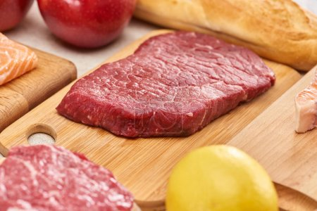 Photo for Fresh raw meat on wooden cutting board near lemon6 apples and baguette - Royalty Free Image