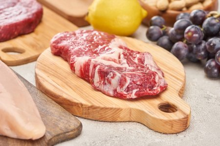 Photo for Raw mmeat tenderloin on wooden cutting board near grapes and lemon on marble surface - Royalty Free Image