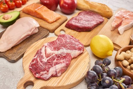 Photo for Fresh raw meat, poultry, fish on wooden cutting boards near lemon, grapes, apples, branch of cherry tomatoes, nuts and french baguette on marble surface - Royalty Free Image