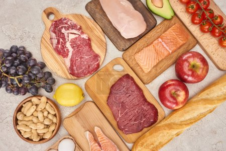 Photo for Top view af raw organic assorted meat, poultry, fish, apples, grape, lemon, avocado, tomatoes and peanuts on wooden cupboards with fresh baguette on marble surface - Royalty Free Image