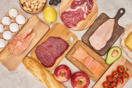 Photo for Top view af raw organic assorted meat, poultry, fish, eggs, apples, lemon, avocado, tomatoes and peanuts on wooden cupboards with fresh baguette on marble surface - Royalty Free Image