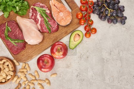 Photo for Top view of assorted meat, poultry and fish with greenery on wooden cutting board near apples, grapes, peanuts, cherry tomatoes and half of avocado on gray marble surface - Royalty Free Image
