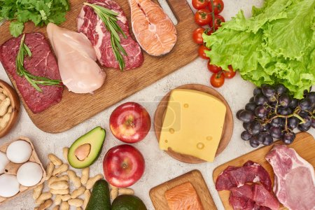 Photo for Top view of assorted meat, poultry and fish with greenery and cheese on wooden cutting boards near apples, grapes, peanuts, cherry tomatoes, eggs and avocados on gray marble surface - Royalty Free Image