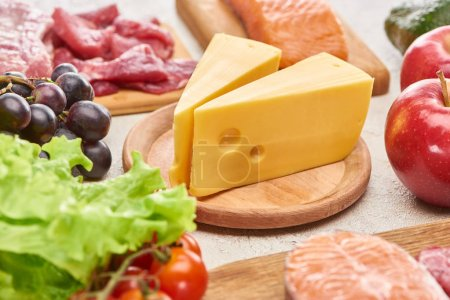 Cheese on wooden cutting board near assorted meat, fish fruits and vegetables