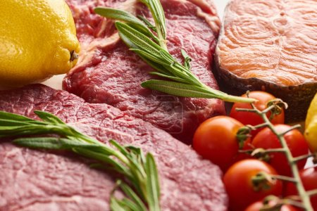 Photo for Close up view of raw meat with rosemary twigs near salmon, lemon and branch of tomatoes - Royalty Free Image