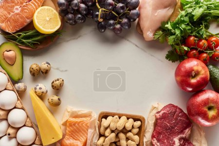 Photo for Top view of assorted raw meat, poultry and fish with eggs, avocados, lemon, cheese, grapes, peanuts, branch of tomatoes and greenery twigs - Royalty Free Image