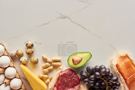 Photo for Top view of raw meat and fish with eggs, avocado, cheese, grapes and peanuts - Royalty Free Image
