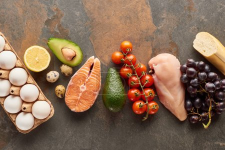 Photo for Top view of raw fish and poultry near vegetables, fruits, eggs and baguette on marble surface with copy space - Royalty Free Image