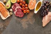 """Постер, картина, фотообои """"Вид сверху сырого мяса, рыбы и птицы возле овощей, фруктов, яиц и оливкового масла на мраморной поверхности с копировальной площадкой"""""""