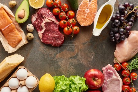 Photo for Top view of raw fish, meat and poultry near vegetables, fruits, eggs, greenery, baguette and olive oil on marble surface with copy space - Royalty Free Image