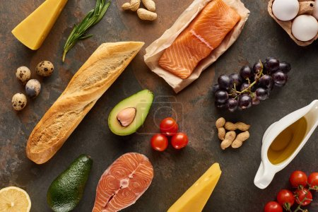 Top view of raw fish near vegetables, fruits, eggs, cheese, peanuts, baguette and olive oil on marble surface