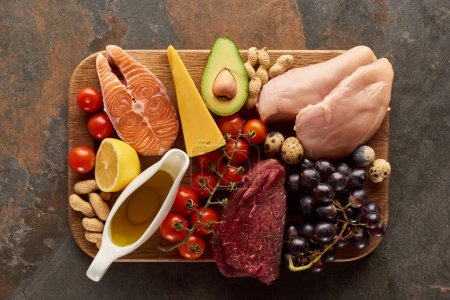 Photo for Top view of raw meat, fish, poultry, cheese, fruits, vegetables with olive oil and peanuts on wooden cutting board on dark brown marble surface - Royalty Free Image