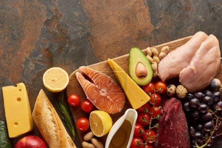 Photo for Top view of wooden cutting board with raw meat, fish, poultry, cheese, fruits, vegetables and peanuts near fresh baguette on dark brown marble surface with copy space - Royalty Free Image