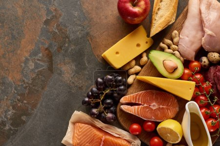 Photo for Top view of wooden cutting board with raw fish, poultry, cheese, fruits, vegetables, baguette and peanuts on dark brown marble surface with copy space - Royalty Free Image