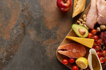Photo for Top view of wooden cutting board with raw fish, poultry, cheese, fruits, vegetables, olive oil, baguette and peanuts on dark brown marble surface with copy space - Royalty Free Image