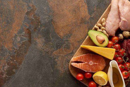 Photo for Top view of wooden cutting board with raw fish, poultry, cheese, vegetables, olive oil and peanuts on dark brown marble surface with copy space - Royalty Free Image