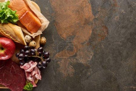 Photo pour Vue supérieure de la planche à découper en bois avec le poisson cru, la viande, le bacon, le fromage, les fruits, les oeufs de caille, la baguette et la laitue sur la surface de marbre brun foncé avec l'espace de copie - image libre de droit