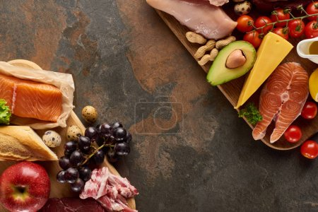 Photo for Top view of wooden cutting boards with raw fish, poultry, cheese, fruits, vegetables, bacon, olive oil, baguette, quail eggs and peanuts on dark brown marble surface with copy space - Royalty Free Image