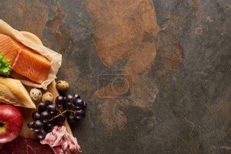 Photo pour Vue supérieure de la planche à découper en bois avec le poisson cru, le bacon, le raisin, la pomme, la baguette et les oeufs de caille sur la surface de marbre brun foncé avec l'espace de copie - image libre de droit