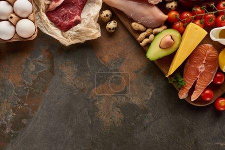 Photo pour Vue supérieure de la planche à découper en bois avec le poisson cru, la viande, la volaille, le fromage, les oeufs, les légumes et les arachides sur la surface de marbre brun foncé avec l'espace de copie - image libre de droit
