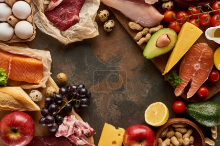 Photo for Top view of wooden cutting board with raw fish, meat, poultry, cheese, fruits, vegetables, olive oil, eggs, baguette and peanuts on dark brown marble surface with copy space - Royalty Free Image