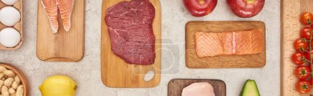 Photo for Panoramic shot of  wooden cutting boards with meat and fish near vegetables on marble surface - Royalty Free Image