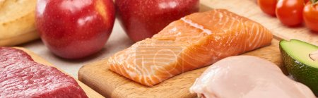 Photo for Panoramic shot of raw salmon near meat, poultry and vegetables on wooden cutting boards - Royalty Free Image