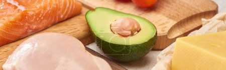 Photo for Panoramic shot of avocado half near wooden cutting boards with fish and poultry - Royalty Free Image